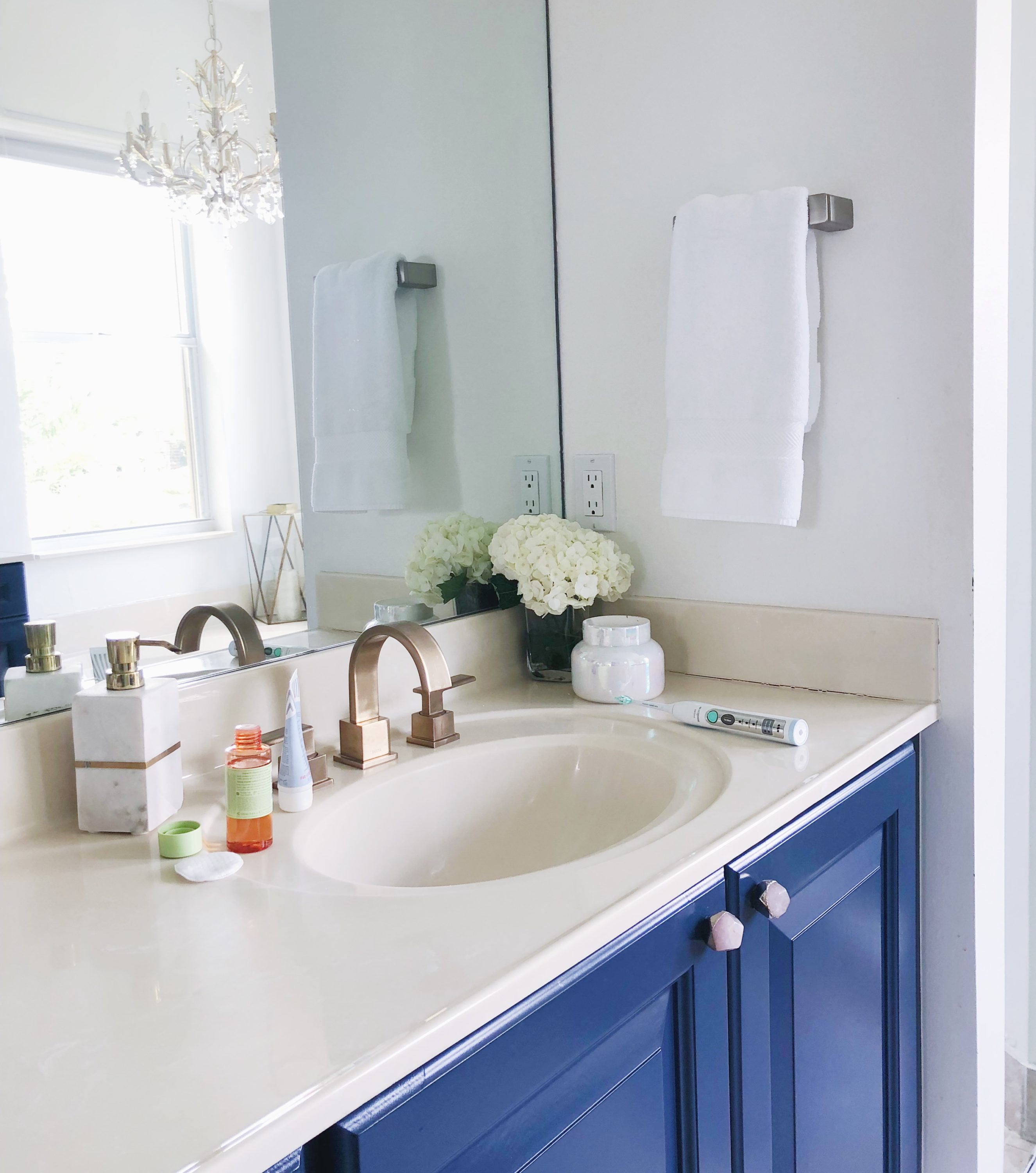Master Bathroom with DIY blue cabinets and gold hardware | Avon | My Nighttime Routine featured by popular Florida life and style blogger The Modern Savvy
