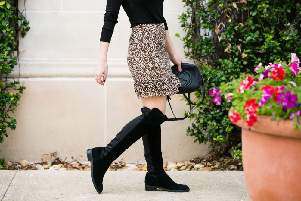 Leopard Print Skirt featured by top US fashion blog The Modern Savvy; Image of a woman wearing Bloomingdales Skirt, BP ribbed long sleeve tee, Blondo knee high riding boots and Gucci bag.