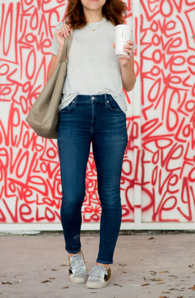 White Tee and Jeans featured by top US fashion blog The Modern Savvy; Image of a woman wearing Something Navy tee, Citizens for Humanity jeans and Shein shoes.