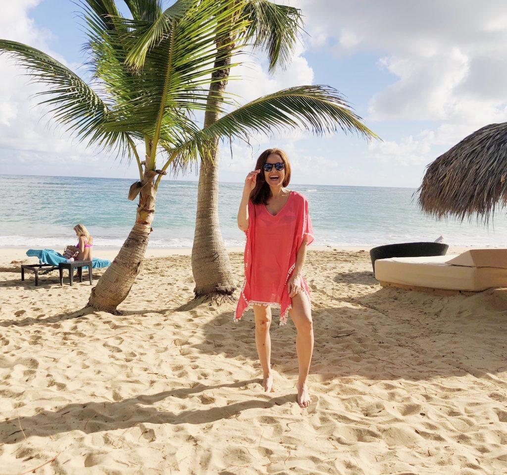 What to Wear in Punta Cana featured by top US fashion blog The Modern Savvy; Image of a woman wearing pom-pom cover up from Amazon.