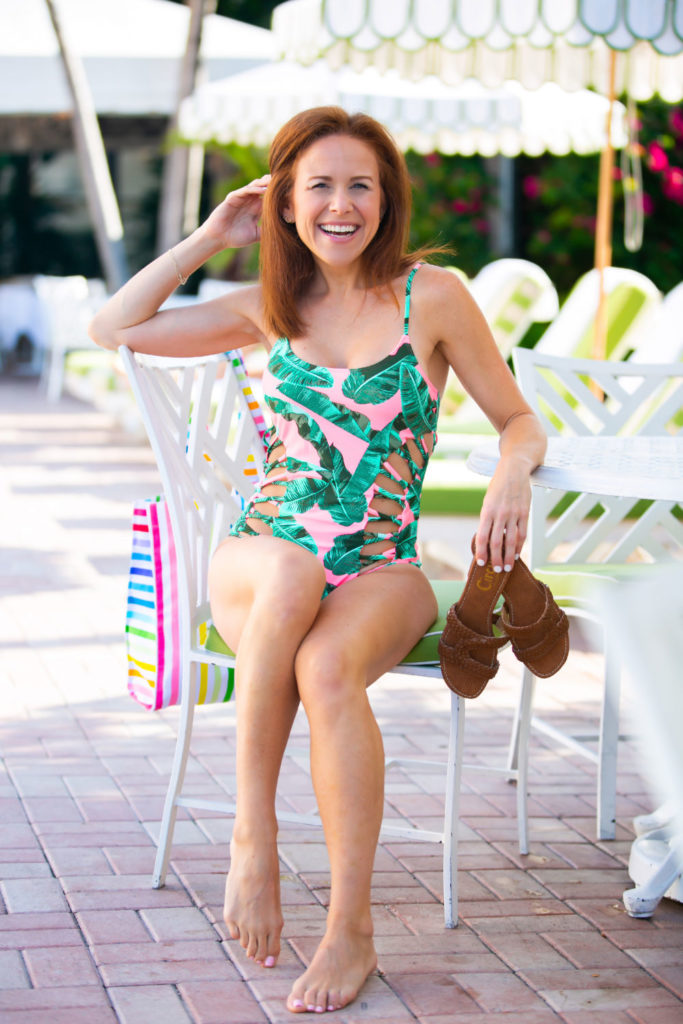 Cute One Piece Swimsuits for the Summer by popular lifestyle blog, The Modern Savvy: image of woman sitting in a poolside lounge chair wearing a pink and green Walmart palm leaf print one piece swimsuit.