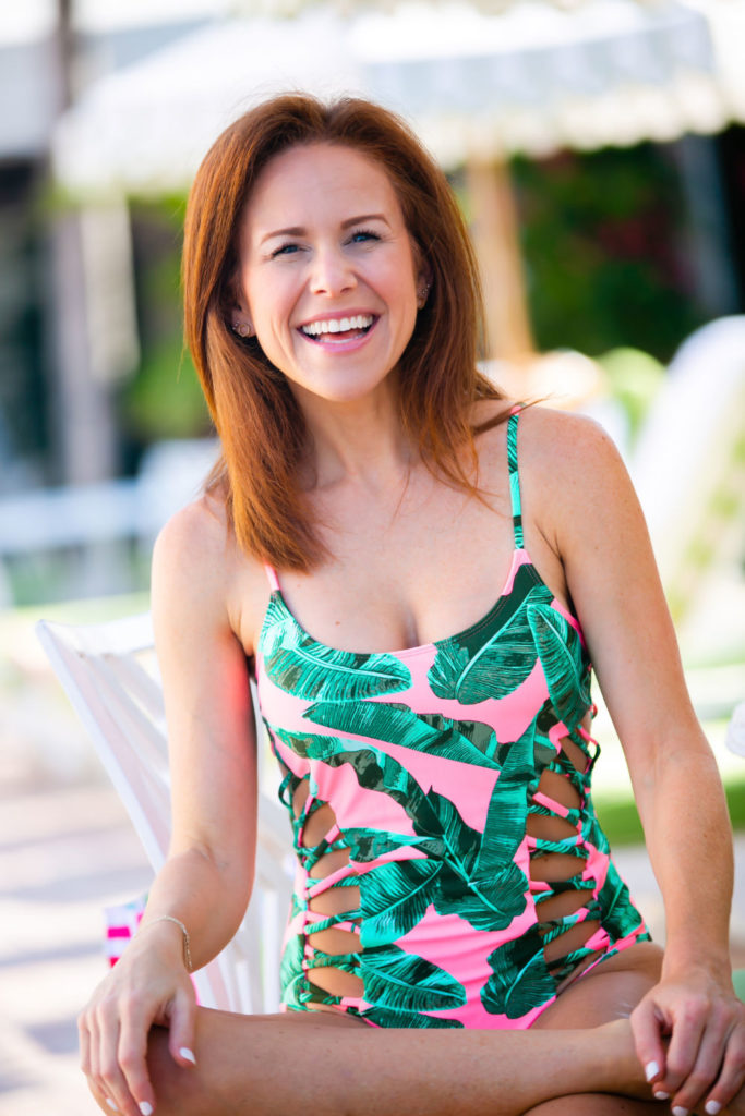 Cute One Piece Swimsuits for the Summer by popular lifestyle blog, The Modern Savvy: image of woman standing by a pool and wearing a pink and green Walmart palm leaf print one piece swimsuit.
