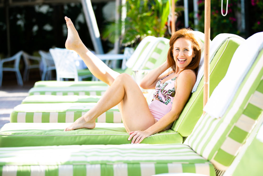 Cute One Piece Swimsuits for the Summer by popular lifestyle blog, The Modern Savvy: image of a woman in a poolside lounge chair and wearing a pink and green tropical print cut out one piece swimsuit from Walmart.