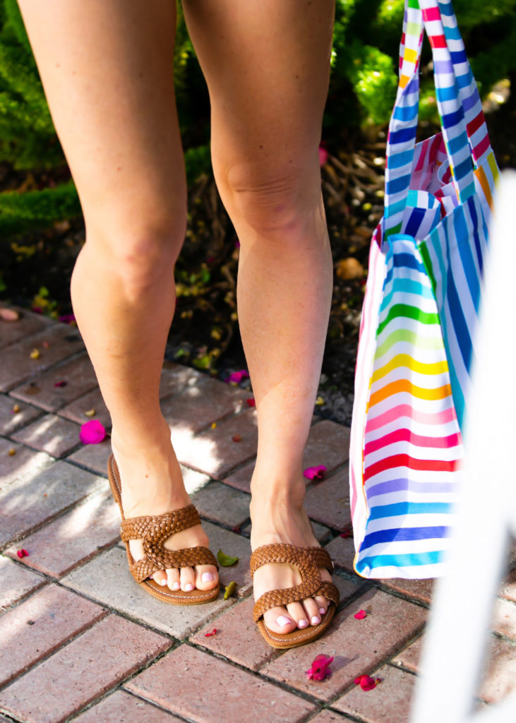 Cute One Piece Swimsuits for the Summer by popular lifestyle blog, The Modern Savvy: image of woman standing by a pool and wearing brown woven sandals and holding a rainbow striped tote from Walmart.