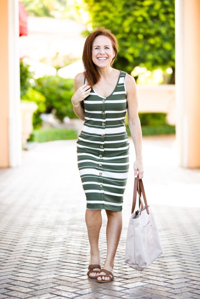 The $9 Striped Midi Dress by popular Florida fashion blog, The Modern Savvy: image of a woman walking outside and wearing a Wal-mart Say What? Juniors' Stripe Knit Button Front Midi Dress, Women's Circus by Sam Edelman Betty-2 Slide Sandals, and Time and Tru Emiko Tote.