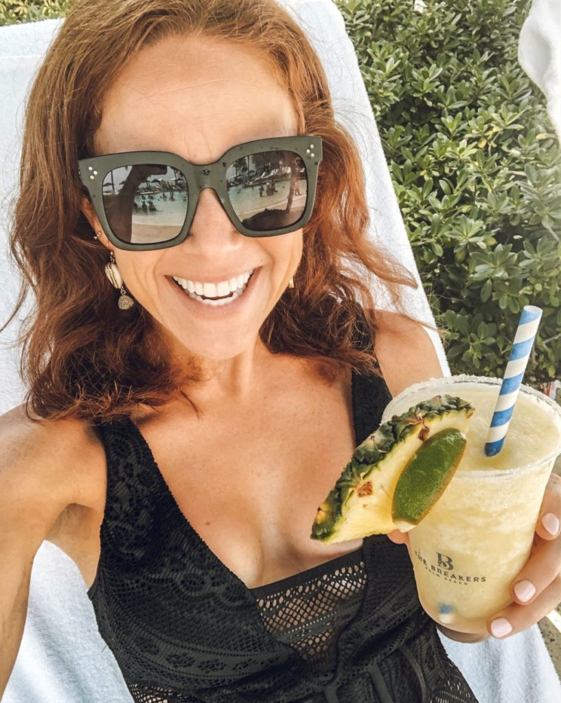 Alyson's Recent Favorites // July 2019 by popular Florida lifestyle blog: The Modern Savvy: image of a woman lounging in a pool chair, holding a cocktail and wearing a pair of Celine sunglasses.