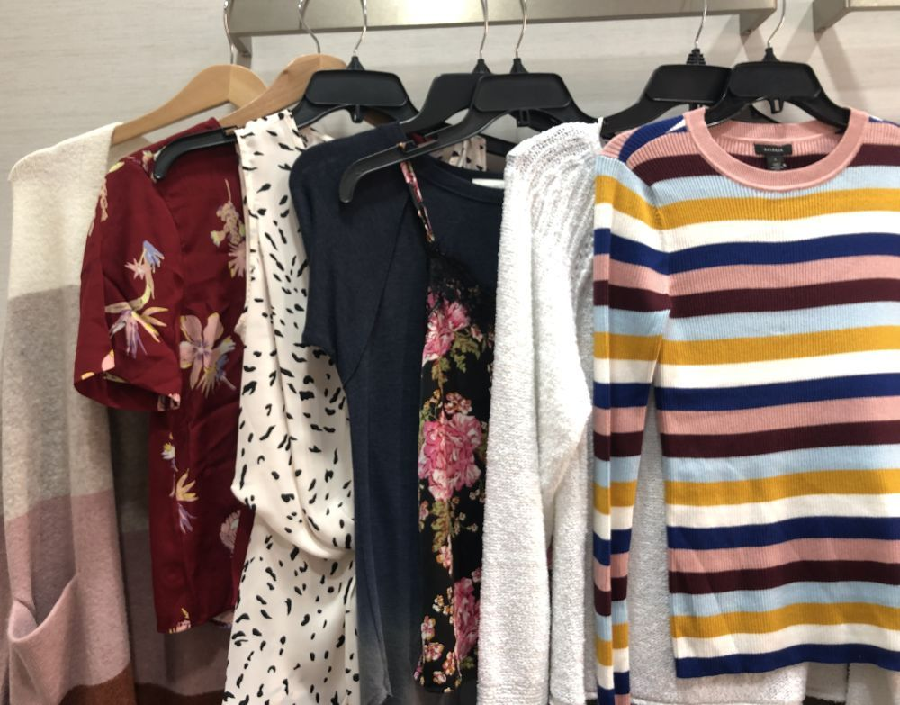 Nordstrom Anniversary Sale 2019: Fitting Room Try-On Session & My Favorite Under $100 finds! by popular Florida fashion blog, The Modern Savvy: image of shirts hanging on clothing rack inside a Nordstrom changing room.