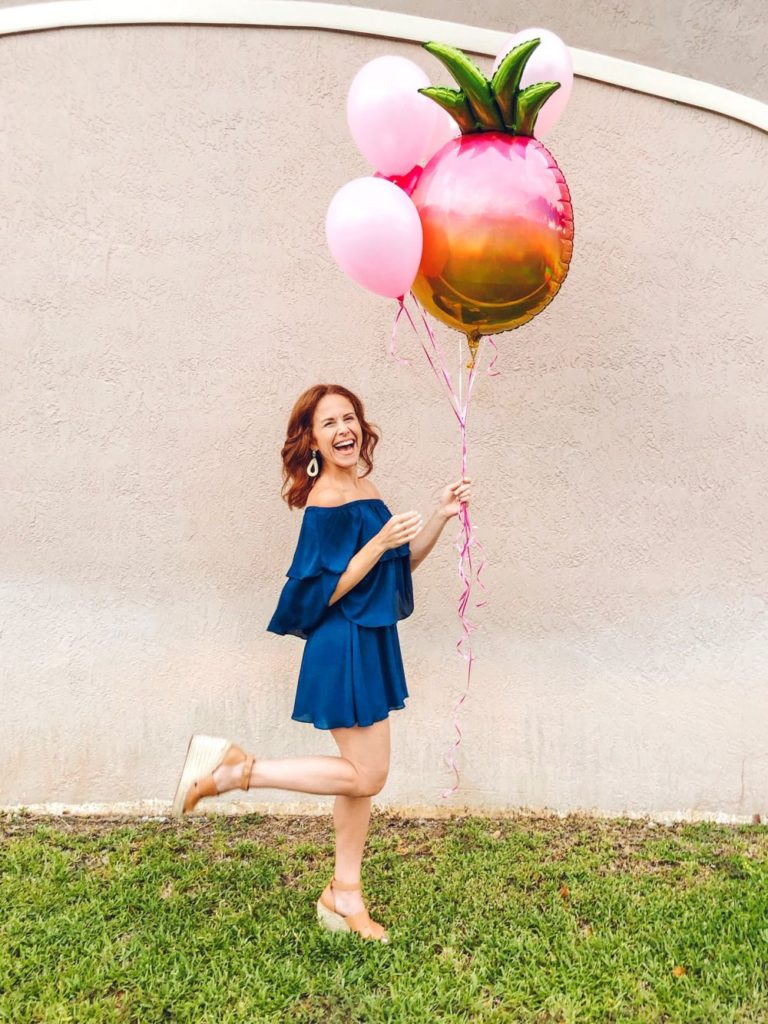 Alyson's Recent Favorites // July 2019 by popular Florida lifestyle blog: The Modern Savvy: image of a woman standing outside and holding a pink balloon bouquet with a giant Mylar pineapple balloon in it.