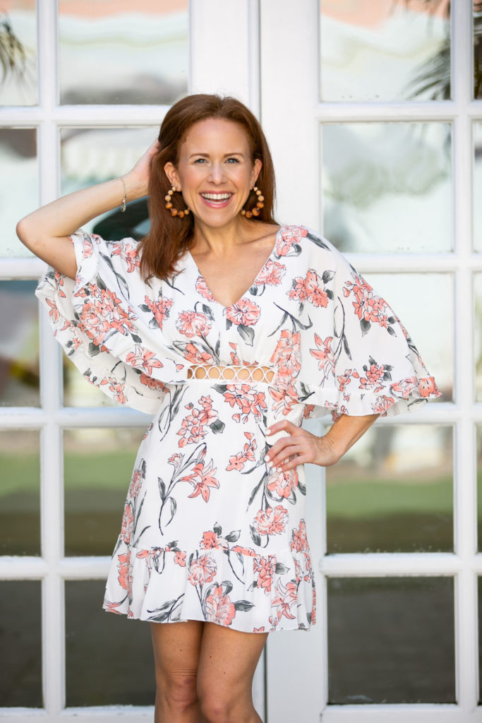 Cute Date Night Dresses Under $35 by popular Florida style blog, The Modern Savvy: image of a woman standing outside and wearing a BTFBM Women Fashion Floral Print V Neck Hollow Out High Waist Ruffle Boho Flowy Short Dress, ShopBop Shashi Rio Hoop Earrings, and Revolve clear strap heels.
