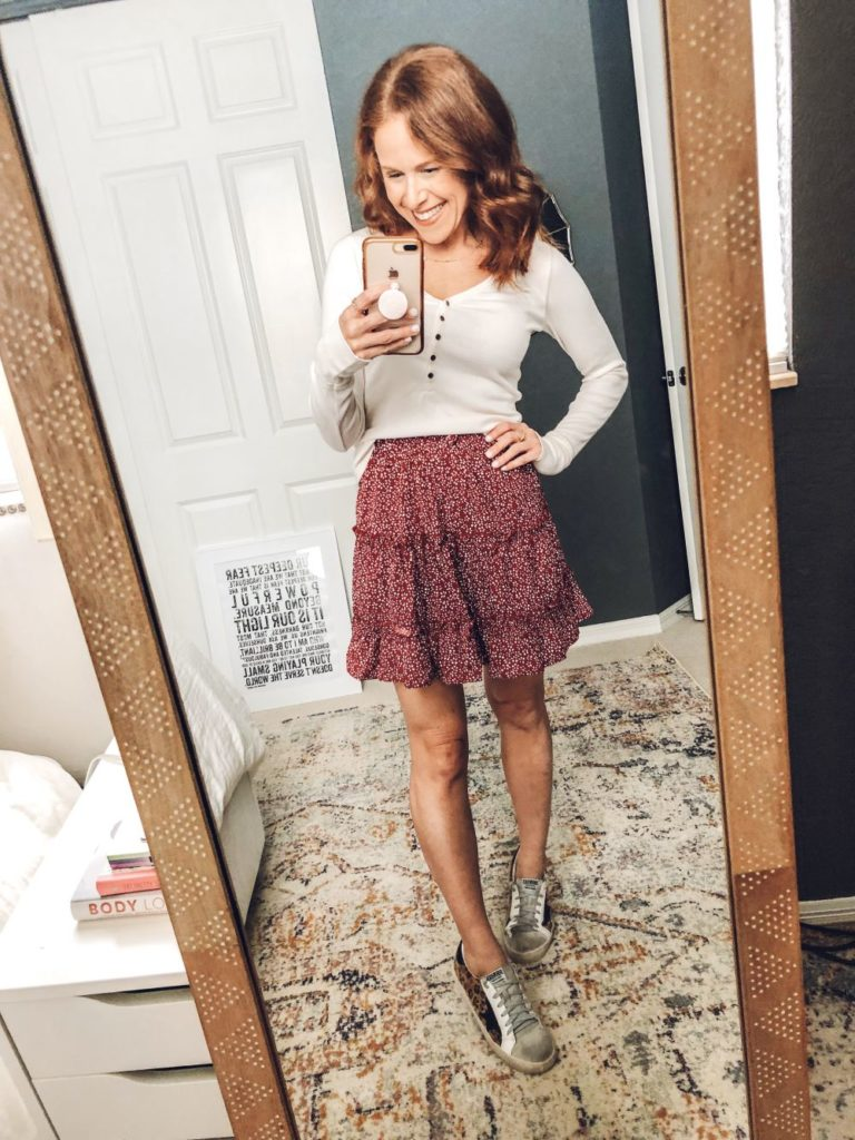 Five Ways to Wear for Fall: The Cutest Under $20 Amazon Skirt by popular Florida fashion blog, The Modern Savvy: image of a woman wearing a Amazon Salamola Women's Leopard Asymmetrical Ruffles High Waist Printed Cute Casual Mini Skirt, Abercrombie and Fitch Long-Sleeve Henley, and sneakers.