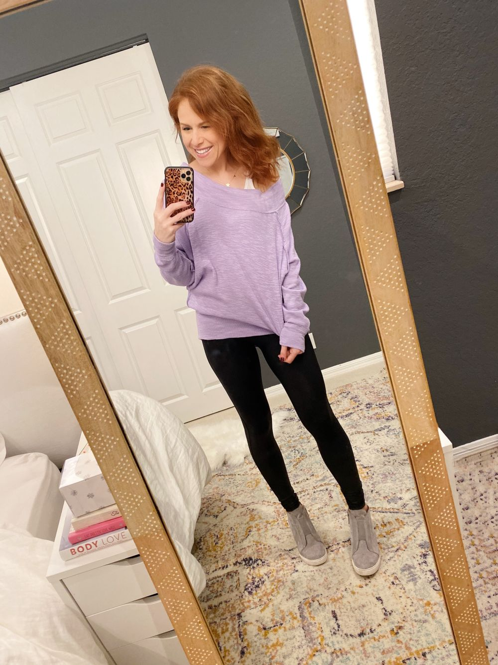 How to Style Spanx Leggings by popular Florida fashion blog, The Modern Savvy: image of a woman wearing Nordstrom Faux Leather Leggings SPANX®, purple tunic, Nordstrom Felicia Wedge Bootie and holding a phone in a Amazon Sonix Watercolor Leopard Case for iPhone 11 Pro.