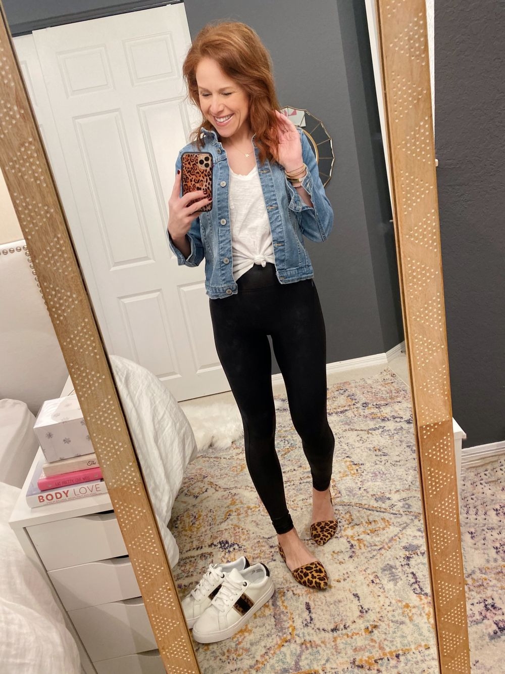 How to Style Spanx Leggings by popular Florida fashion blog, The Modern Savvy: image of a woman wearing Nordstrom Faux Leather Leggings SPANX®, denim jacket, Nordstrom Madewell Whisper Cotton V-Neck Pocket Tee, Nordstrom Gojana Super Star Pendant Necklace, J. Crew Zoe calf hair d'Orsay flats and holding a phone in a Amazon Sonix Watercolor Leopard Case for iPhone 11 Pro.