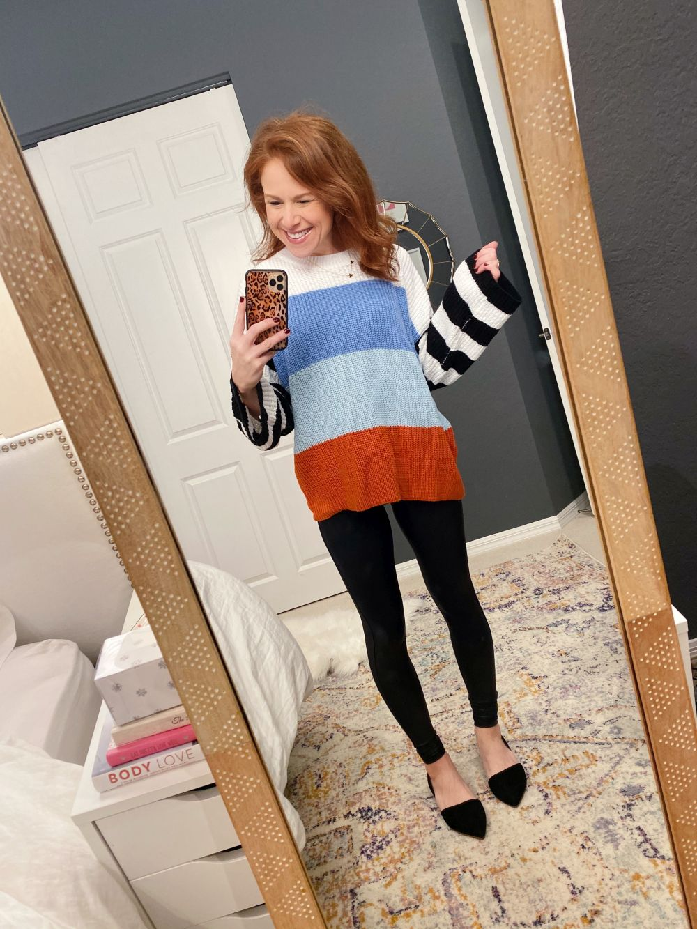 How to Style Spanx Leggings by popular Florida fashion blog, The Modern Savvy: image of a woman wearing Nordstrom Super Star Pendant Necklace GORJANA, Amazon ZESICA Women's Long Sleeve Crew Neck Striped Color Block Casual Loose Knitted Pullover Sweater, Nordstrom Faux Leather Leggings SPANX®, J. Crew Zoe suede d'Orsay flats, and holding a phone in a Amazon Sonix Watercolor Leopard Case for iPhone 11 Pro.