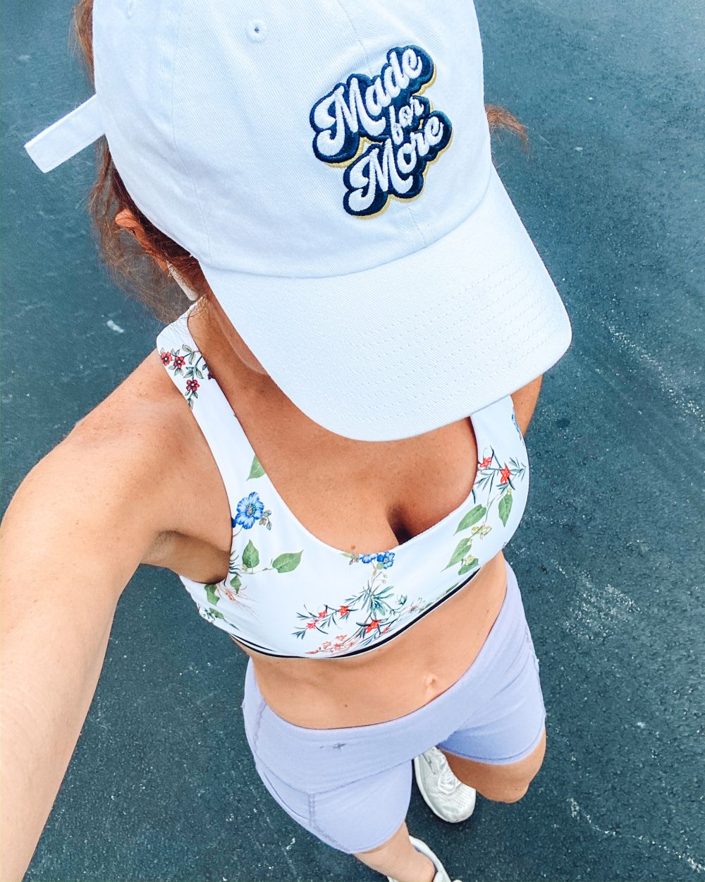 Home Workout Equipment Ideas by popular Florida lifestyle blog, The Modern Savvy: image of a woman wearing a white ball cap, floral bralette, white sneakers, and purple bike shorts.