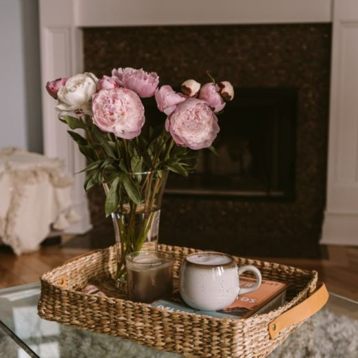 Favorite Weekend Sale by popular Florida life and style blog, The Modern Savvy: image of a vase of peonies in a wicker nesting basket on a glass coffee table.