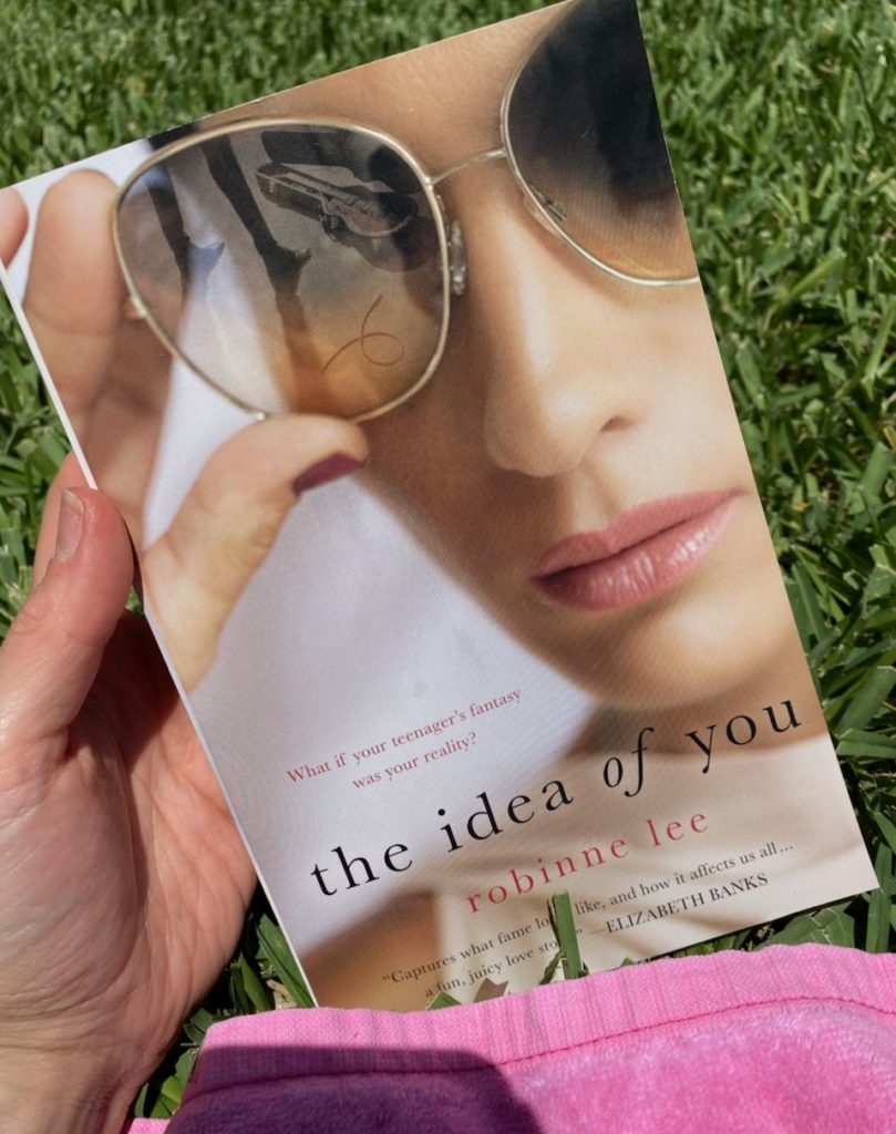 How to Feel Happy Again by popular Florida lifestyle blog, The Modern Savvy: image of a woman holding the book The Idea of You.