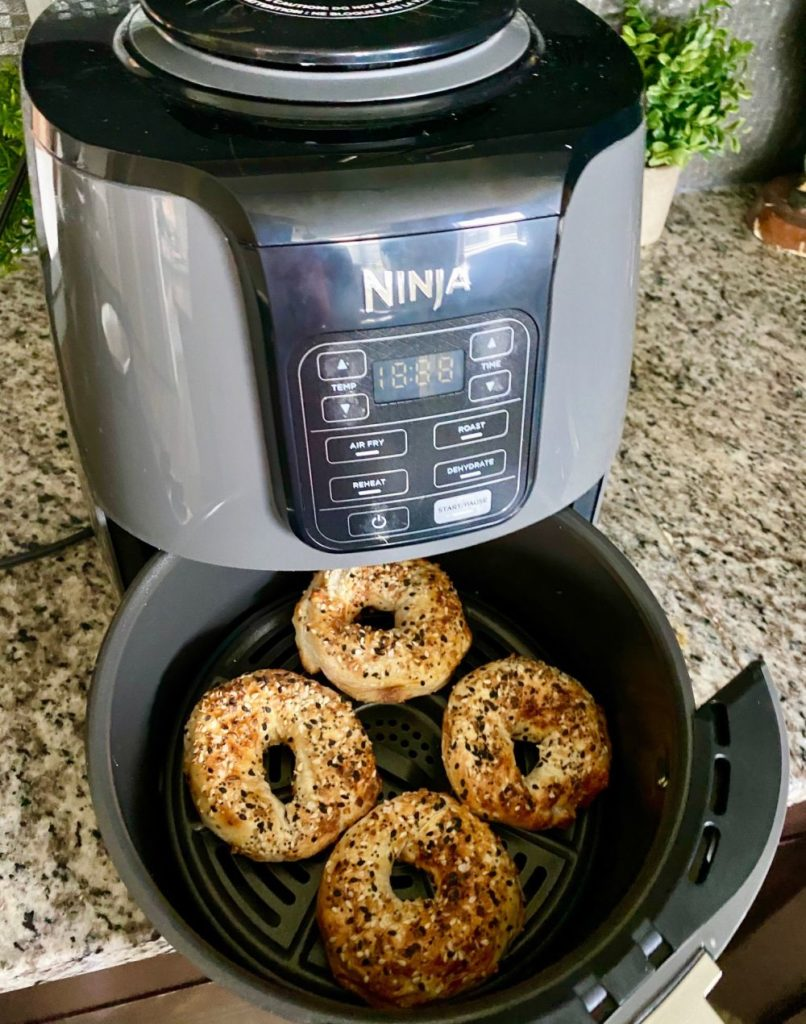 Bagel Recipe by popular Florida lifestyle blog, The Modern Savvy: image of some bagels in a Ninja air fryer.