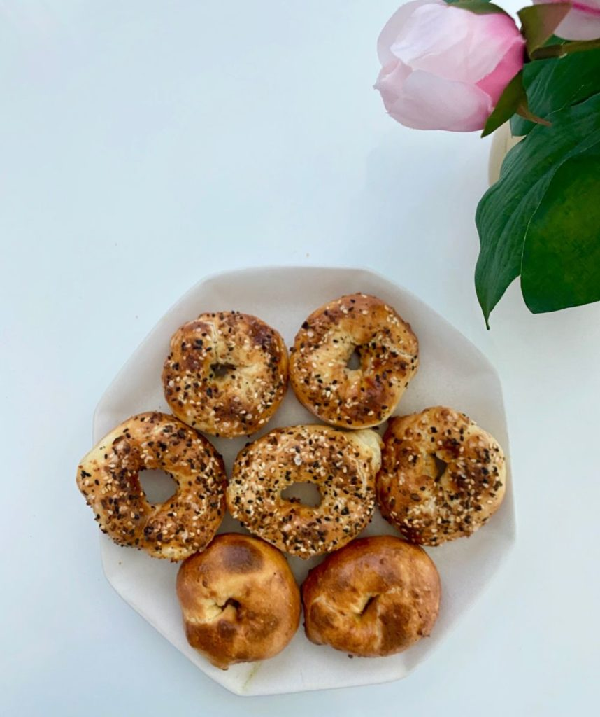 Bagel Recipe by popular Florida lifestyle blog, The Modern Savvy: image of some bagels on a white ceramic plate.