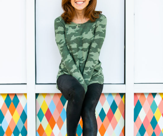 Cyber Week Deals by popular Florida life and style blog, The Modern Savvy: image of a woman wearing a long sleeve camo shirt and black leather leggings with a pair of white sneakers.